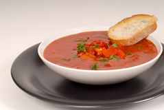 Tomato, red pepper, basil soup in white bowl with bread on a light gray background stock photography