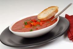Tomato, red pepper, basil soup in white bowl with bread and spoo Stock Photo