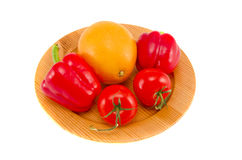 Tomato,red  peppers and grapefruit on wooden plate Royalty Free Stock Photo