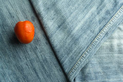 Tomato red on striped denim folded into a triangle. Stock Images