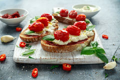 Tomato Ricotta Bruschetta with sun dried tomatoes paste, olive oil brown bread and basil in a white wooden board. Stock Photos