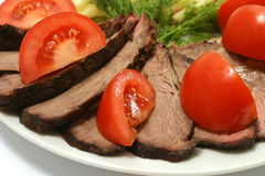 Tomato and roast beef. Sliced roast meat and tomato on dish Stock Photography