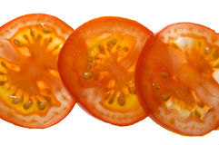 Tomato row. Three tomato slices in a white table with backlit Stock Photos