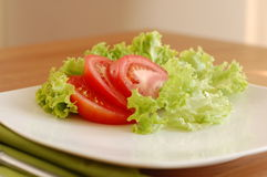 Tomato and salad. Slices of fresh, red tomato served with green salad leaves on a white plate Stock Photos