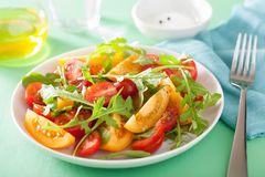 Tomato salad with arugula over green background Stock Image