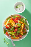 Tomato salad with arugula over green background Stock Photos