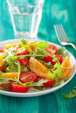 Tomato salad with arugula over green background Royalty Free Stock Photos