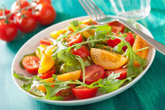 Tomato salad with arugula over green background Royalty Free Stock Images