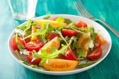 Tomato salad with arugula over green background Stock Photo