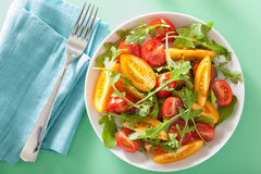 Tomato salad with arugula over green background Royalty Free Stock Photography