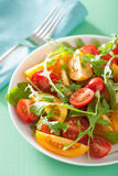 Tomato salad with arugula over green background Royalty Free Stock Photo
