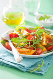 Tomato salad with arugula over green background Royalty Free Stock Image