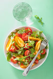 Tomato salad with arugula over green background Stock Photo