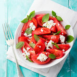 Tomato salad with basil, cheese, olive oil and garlic dressing. Blue wooden background. Top view. Stock Image