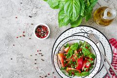 Tomato salad with basil and pine nuts in bowl - healthy vegetarian vegan diet organic food appetizer. Top view. Flat lay stock image