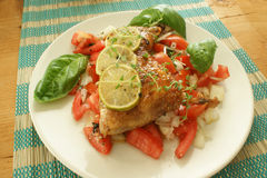 Tomato salad with chicken and grilled lemon stock photos