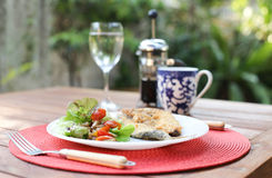 Tomato salad and fish steak with on plate Royalty Free Stock Photos