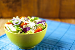Tomato salad. In green bowl on blue mat with wooden background Royalty Free Stock Photos