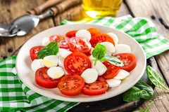 Tomato salad with mozzarella cheese and olive oil. Italian cuisine Royalty Free Stock Photos