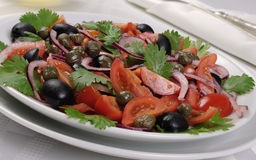 Tomato salad with olives, capers and cilantro Stock Photos
