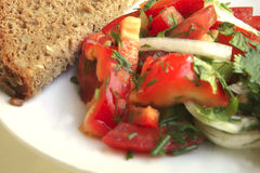 Tomato salad and rye bread. On white table Royalty Free Stock Photography