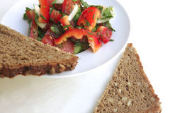 Tomato salad and rye bread. On white table Royalty Free Stock Images