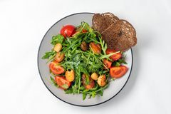 Tomato salad with shrimps, arugula and rye rusk on a white background stock photo
