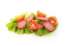 Tomato and Salami. Slices of tomato and salami on a lettuce leaf isolated on a white background Royalty Free Stock Image