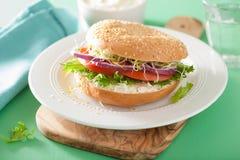 Tomato sandwich on bagel with cream cheese onion lettuce alfalfa Stock Photos