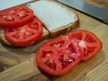 Tomato sandwich slices bread. Making a tomato sandwich with slices of bread with mayonnaise on a cutting board with knife royalty free stock image