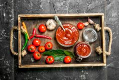 Tomato sauce in a bowl and in a jar on tray. On black rustic background stock image