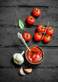 Tomato sauce in bowl with spoon and fresh garlic. On black rustic background royalty free stock photography