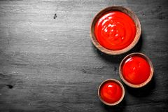 Tomato sauce in bowls. On black background royalty free stock photo