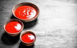 Tomato sauce in bowls. On black background royalty free stock photography
