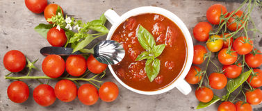 Tomato sauce. Cherry type tomatoes on wooden background with tomato organic home made sauce in a little traditional pot Stock Photo