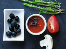 Tomato sauce with dry  basil and  black olives. Royalty Free Stock Image