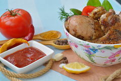 Tomato sauce and fried chicken legs, wings on blue table. Tomato sauce and fried chicken legs, wings near spices on blue table Stock Photography