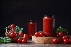 Tomato sauce in a glass jar, tomatoes and herbs on its side. stock photos
