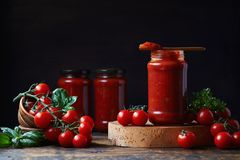 Tomato sauce in a glass jar, tomatoes and herbs on its side. Stock Photography