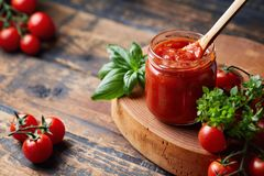 Tomato sauce in a glass jar, tomatoes and herbs on its side. Royalty Free Stock Photo