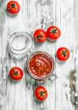 Tomato sauce in a glass jar. On white wooden background stock photography
