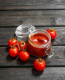 Tomato sauce in a jar with ripe cherry tomatoes. On wooden background stock image