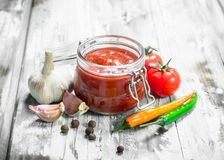 Tomato sauce in a jar and spices. On white wooden background royalty free stock image