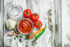 Tomato sauce in a jar and spices. On white wooden background stock photo