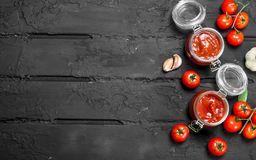 Tomato sauce in a jar of tomatoes. On black rustic background royalty free stock photography