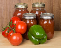 Tomato sauce in jars with tomatoes and peppers Royalty Free Stock Photos