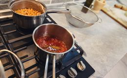 Tomato sauce for pizza is cooked on the stove royalty free stock photos
