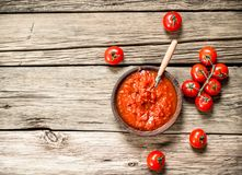 Tomato sauce with spices. On a wooden background royalty free stock photos