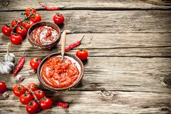 Tomato sauce with spices. On a wooden background stock image