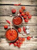 Tomato sauce with spices. On a wooden background royalty free stock image